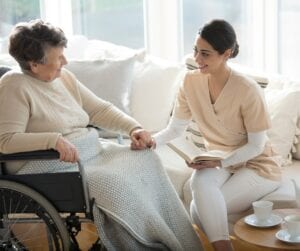 Nurse spending time with elderly woman by reading to her