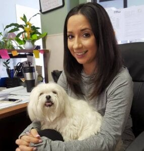 Woman holding small white dog