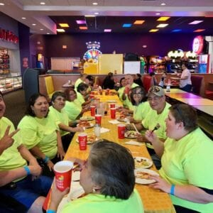 Special needs adults eating pizza and having fun