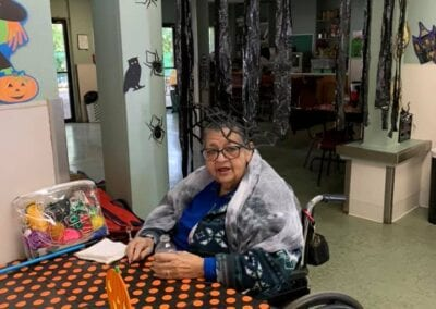 Woman in a wheelchair smiling at Halloween party