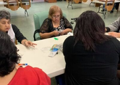 Elderly women playing cards in assisted living facility