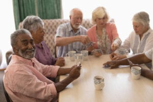 Elderly folks playing cards and smiling together